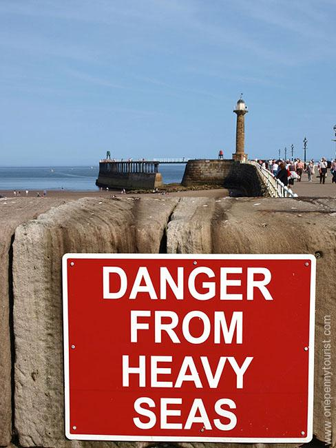 Danger from Heavy Seas Sign on Whitby's Harbour wall in North Yorkshire
