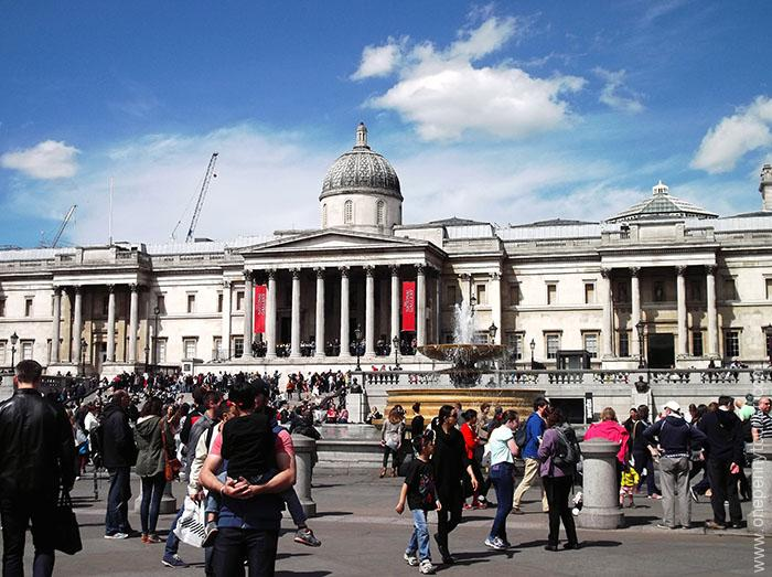 A bustling Trafalgar Square in London, with The National Gallery in the background.