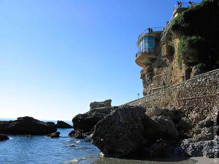 A view of Balcon de Europa from the beach below in Nerja, Spain. OnePennyTourist.com