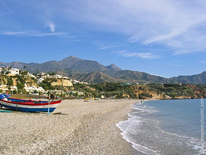 A Nerja beach (Spain) with beautiful mountains in the background. Onepennytourist.com